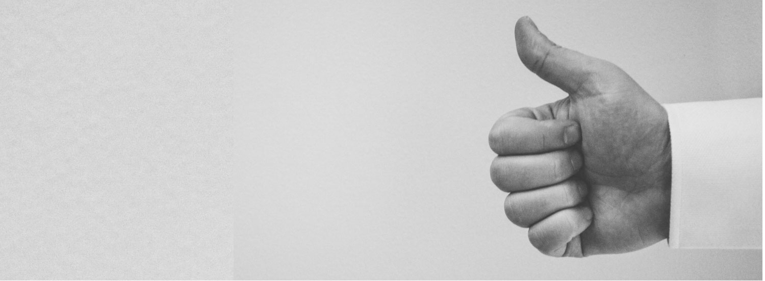 A hand giving a thumbs up on a grey background