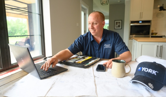 Ben Sauve an HVAC expert reviews work on his laptop
