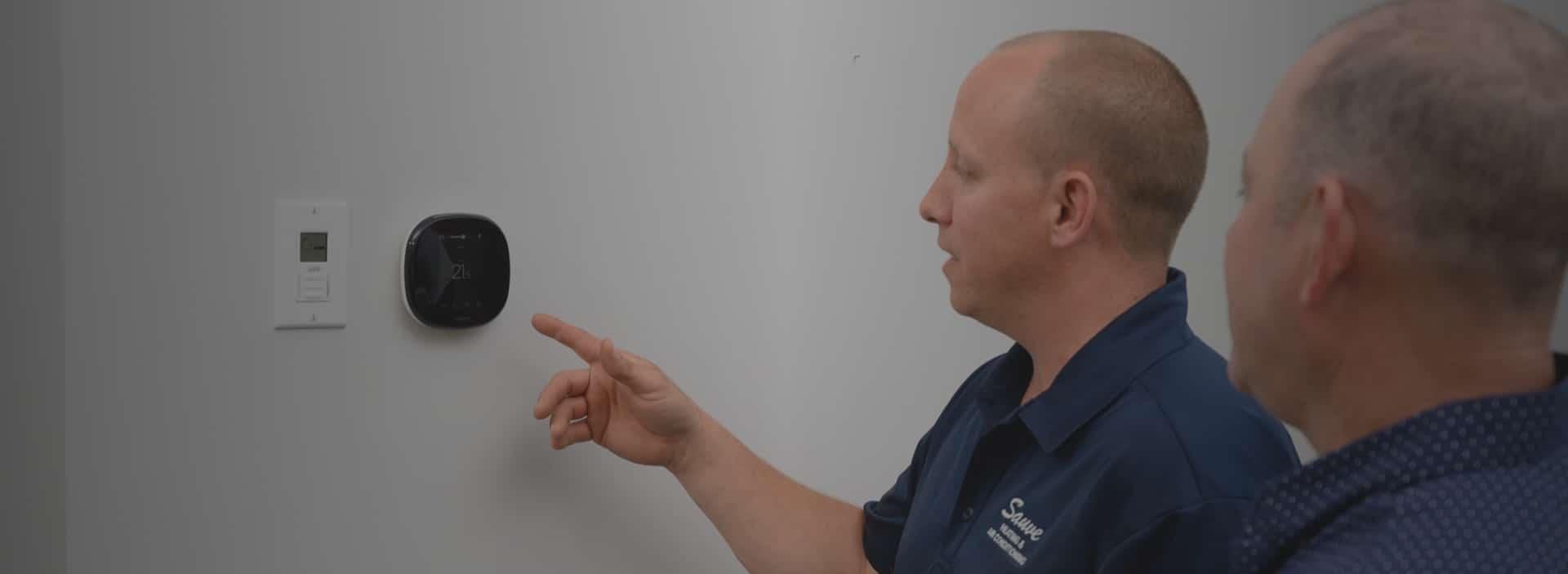 Ben Sauve adjusting the heat in an Ottawa home
