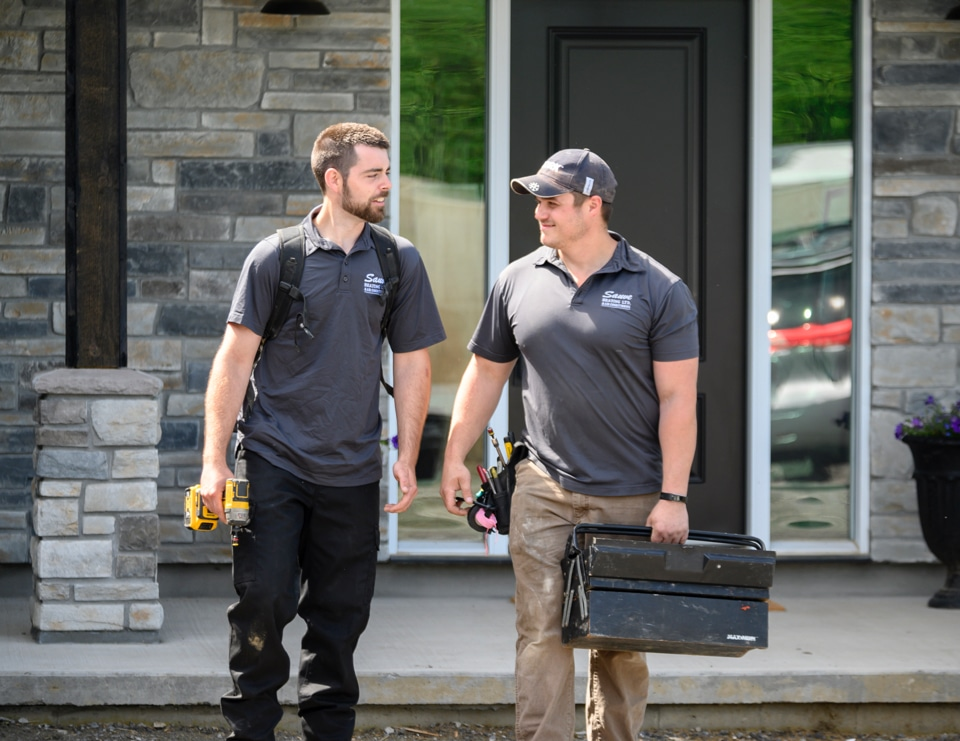 two male HVAC experts on site to install a new water heater at an Ottawa home